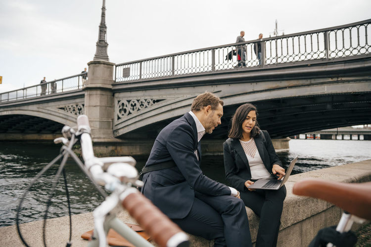 People on bridge over river in city