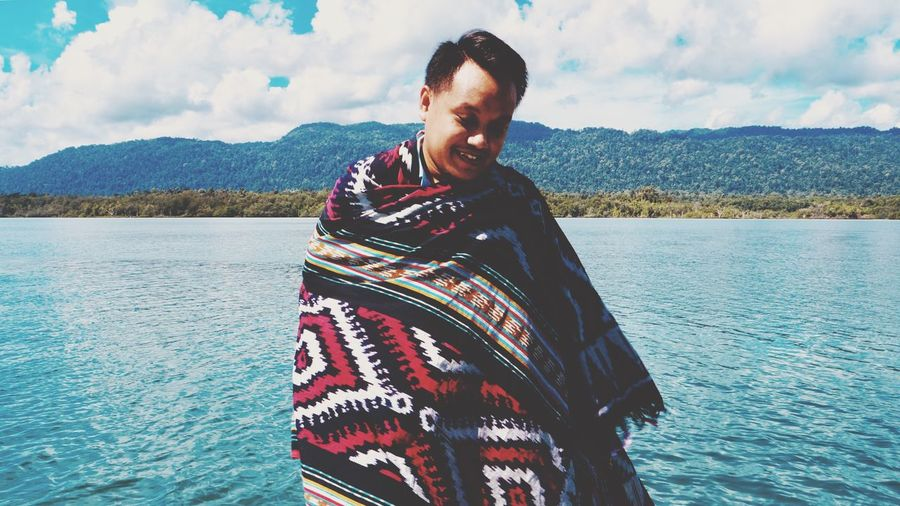 Man wrapped in blanket while standing against lake during winter