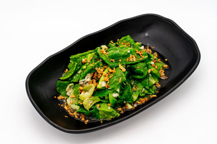 High angle view of green vegetables in bowl against white background