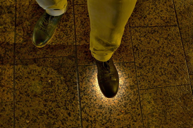 Low section of man standing on yellow surface