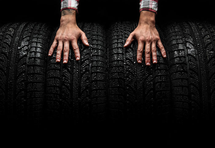 Men's hands on a car tires, studio shot Auto Automobile Black Black Background Classic Four Human Body Part Human Hand Man's Hands Object Protector Rim Rubber Set Shape Studio Shot Texture Textured  Tire Tires Tread Tyre Tyres Unused Winter Tires