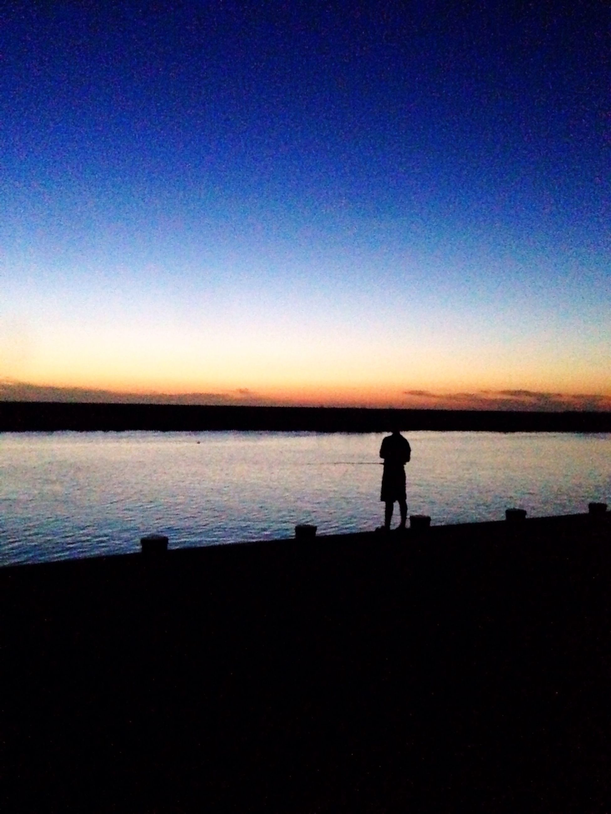 silhouette, water, sunset, scenics, tranquil scene, copy space, tranquility, standing, sea, beauty in nature, clear sky, men, nature, leisure activity, idyllic, dusk, outline, lifestyles, beach
