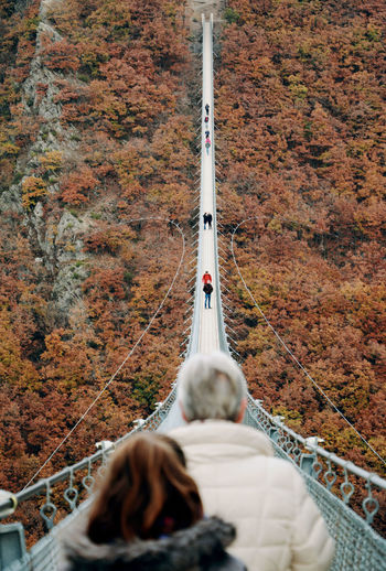Rear View Of People Walking On Suspension Bridge