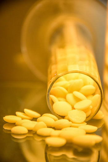 Close-up of yellow pills on table
