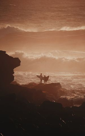 Beauty In Nature Domestic Domestic Animals Land Mammal Men Nature One Animal Outdoors People Pets Real People Scenics - Nature Sea Silhouette Sky Sunset Two People Water