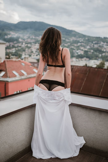 Rear view of seductive woman looking at cityscape while standing on building terrace