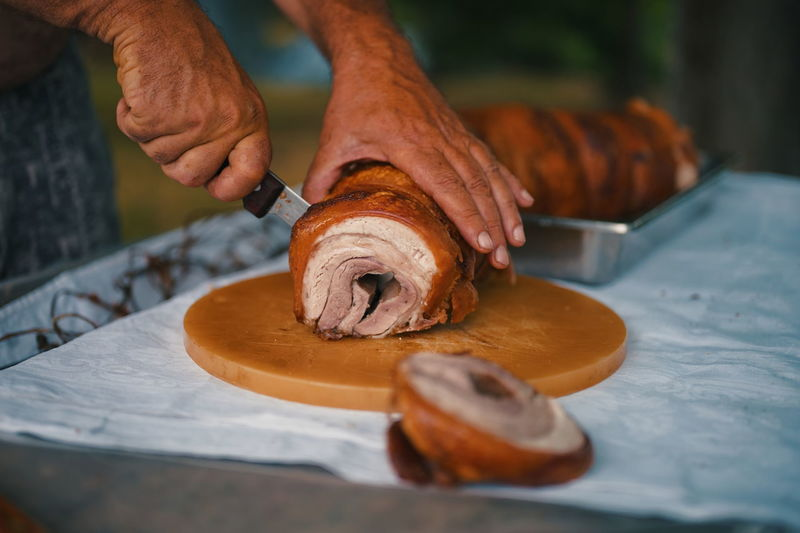 Cropped shot of hands cutting big piece of pork meat on the table in nature