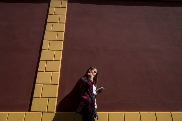 Side view of woman holding book while standing against wall