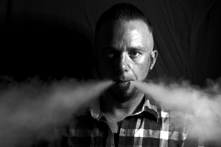 Portrait of bearded man exhaling smoke against curtain