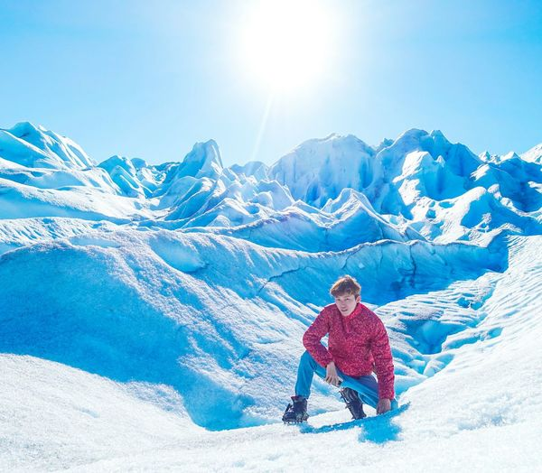 Young Man Kneeling On Moreno Glacier Against Sky During Sunny Day