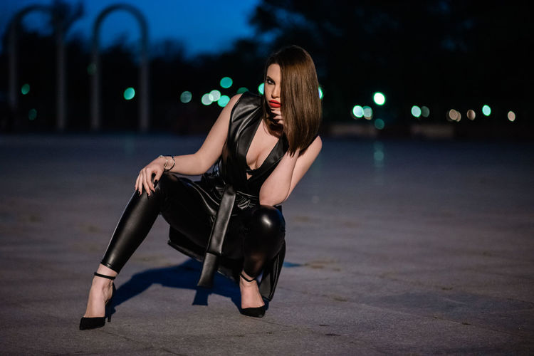 Woman sitting in city at night