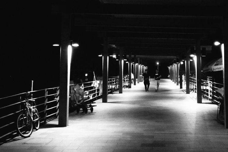 Man walking on illuminated underground walkway