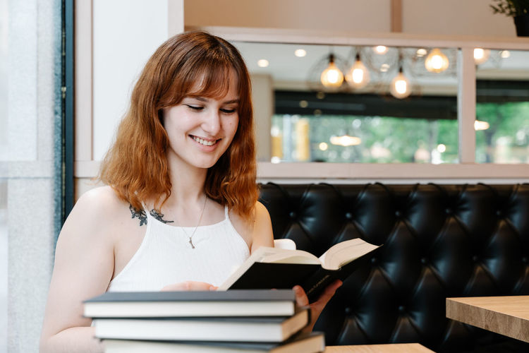 Portrait of smiling young woman sitting on book