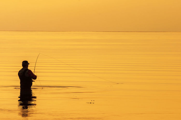 Silhouette man fishing in sea against orange sky