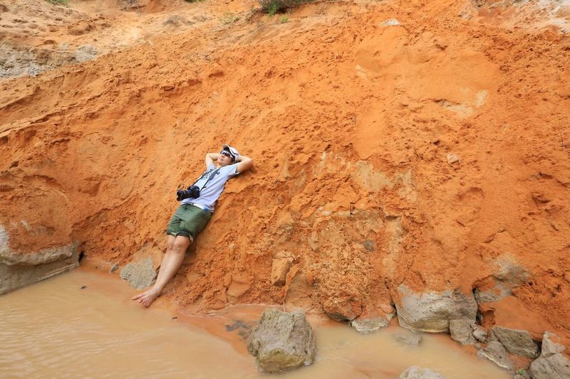 Man relaxing on rock formation by muddy river