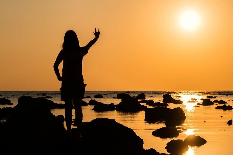 Silhouette woman gesturing while standing at beach against sky during sunset