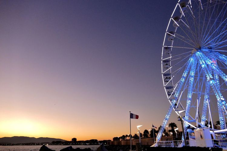 Illuminated Ferris Wheel Against Clear Sky At Sunset