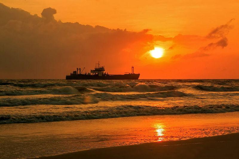 Cargo ship in sea against orange sky during sunset