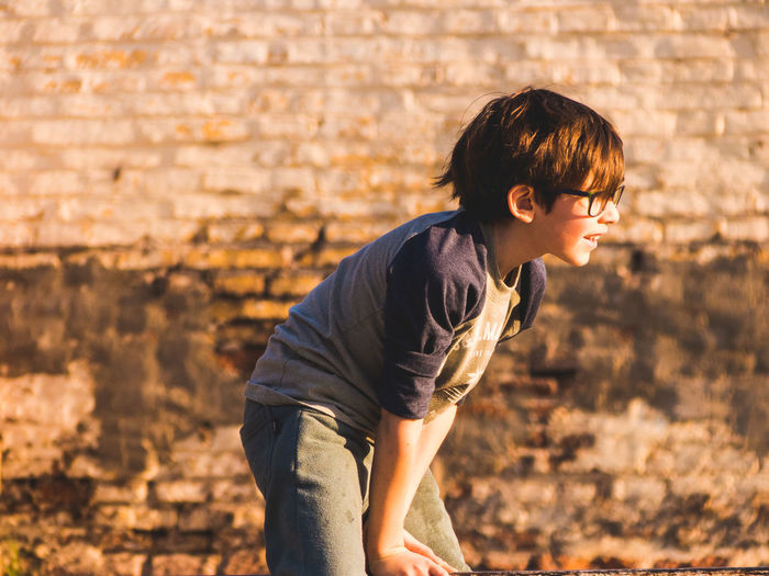 Side view of boy standing against brick wall on sunny day