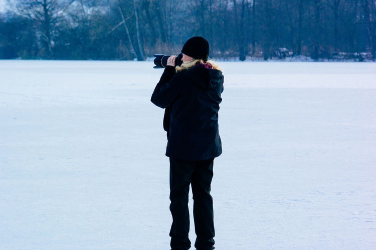 Rear View Of Woman Photographing Ice On Landscape