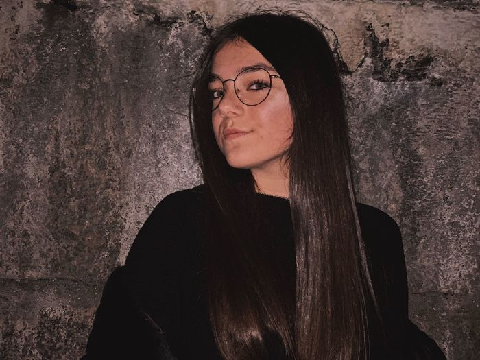 Portrait of beautiful young woman with long hair against wall
