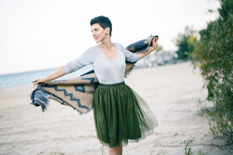 Woman holding scarf while standing at beach