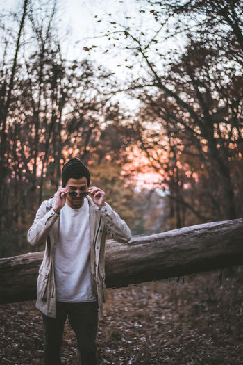 Man wearing sunglasses while standing in forest during sunset