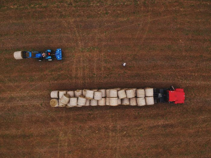Aerial View Of Vehicles Carrying Hay Bales At Farm