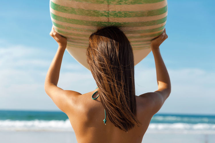 Rear view of young woman holding surfboard while standing at beach against sky