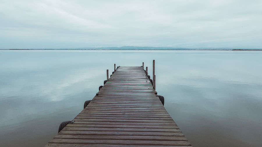 Narrow wooden jetty leading to calm sea against cloudy sky