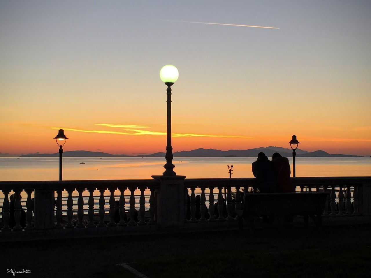 sunset, sea, silhouette, water, railing, sky, nature, beauty in nature, scenics, outdoors, leisure activity, real people, horizon over water, photographing, photography themes, sun, two people, men, beach, lifestyles, vacations, women, togetherness, camera - photographic equipment, coin-operated binoculars, day, people