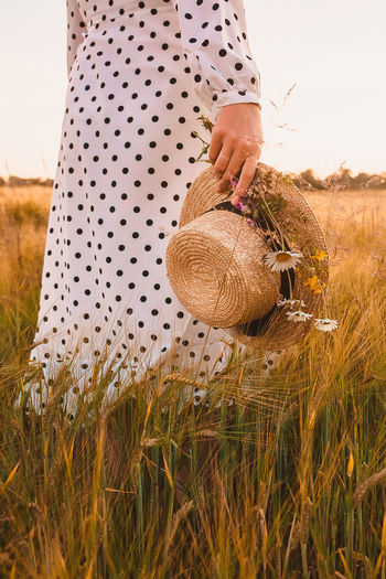 Midsection of woman holding basket on field
