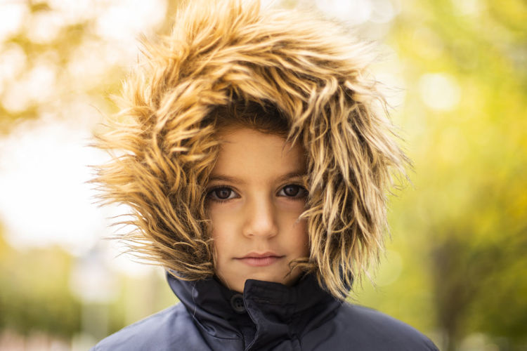 Close-up portrait of smiling boy wearing fur hat