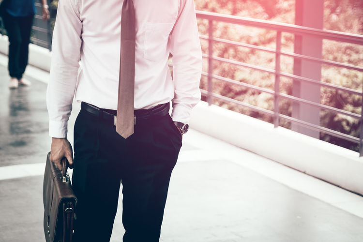 Midsection Of Businessman Holding Briefcase While Standing On Footbridge