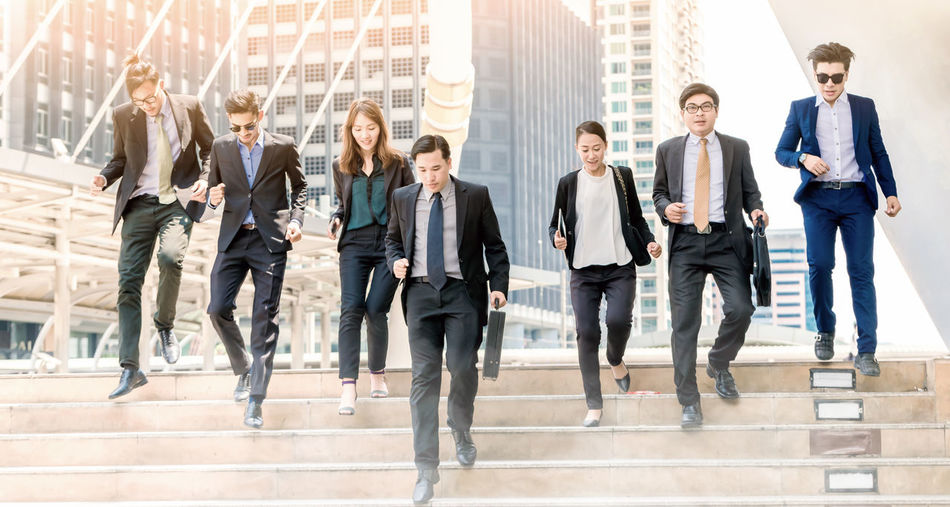 Businesspeople Running On Steps By Buildings In City