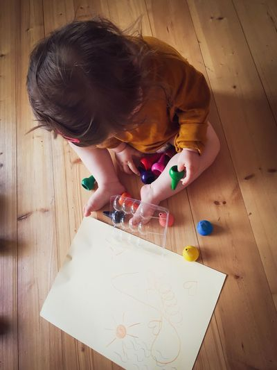 High angle view of child holding paper on table