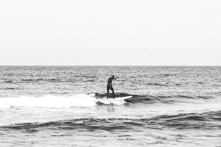 Silhouette man surfing in sea against clear sky