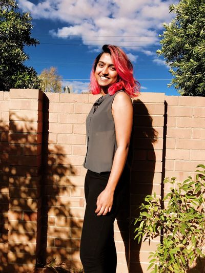 Short pink hair young women happy smiling cheerful in casual clothing black jeans grey top simple