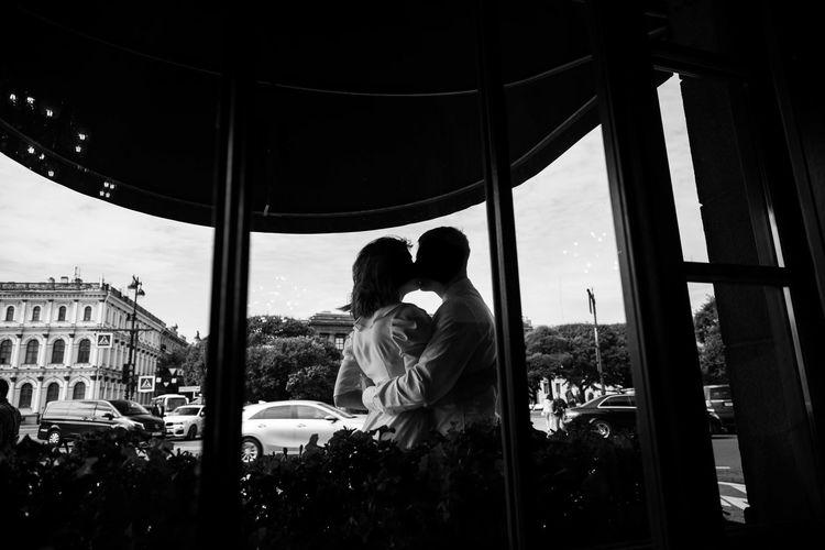 Rear view of couple walking on glass window