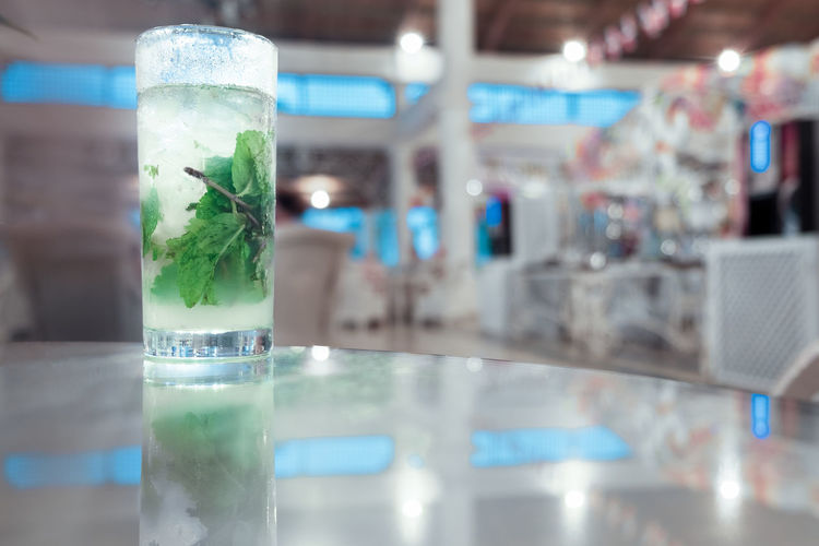 Glass - Material Indoors  Transparent Close-up No People Focus On Foreground Drinking Glass Selective Focus Green Color Drink Table Food And Drink Glass Mojito Herb Mint Leaf - Culinary Alcoholic Drink Copy Space Relaxation Enjoyment Garnish Party - Social Event Bar - Drink Establishment Refreshment Ice