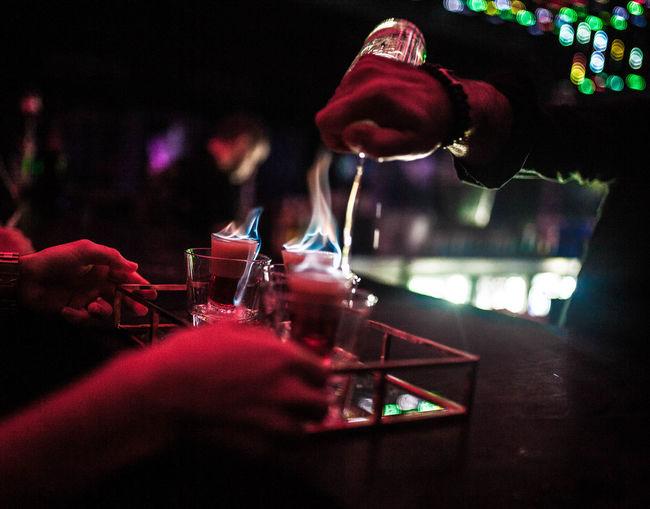 Close-up of hand preparing drink at bar counter