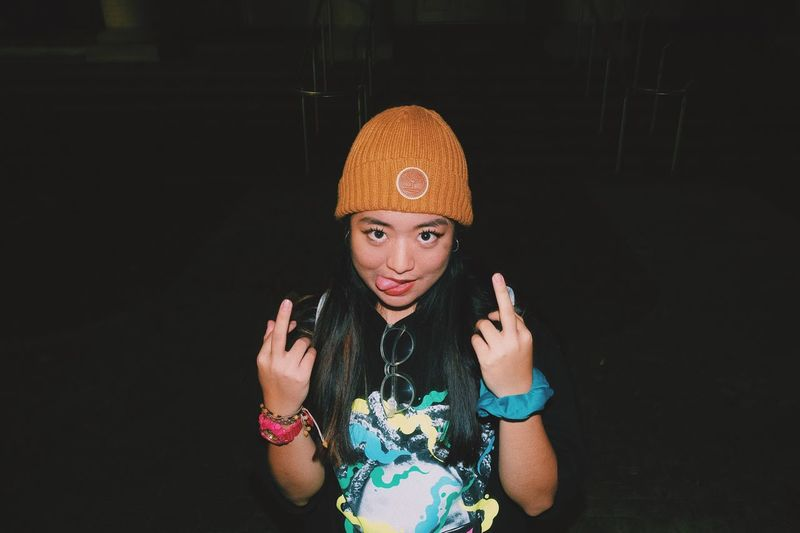 Portrait of woman showing middle fingers at night