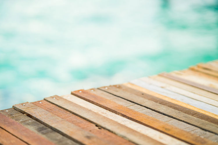 Close up top of wooden deck at sunrise beach. turqoise green sea in the background.