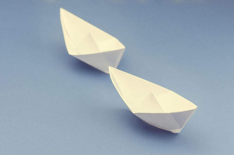paper sail boats on blue sea Art And Craft Blue Blue Background Close-up Colored Background Concept Craft Creativity Cut Out Design Floating On Water Folded High Angle View Indoors  Nature No People Origami Paper Paper Boat Shape Still Life Studio Shot White Color
