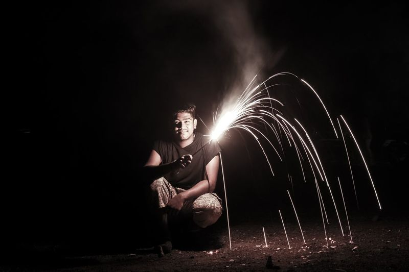 Portrait of mature man holding firework while crouching on field at night