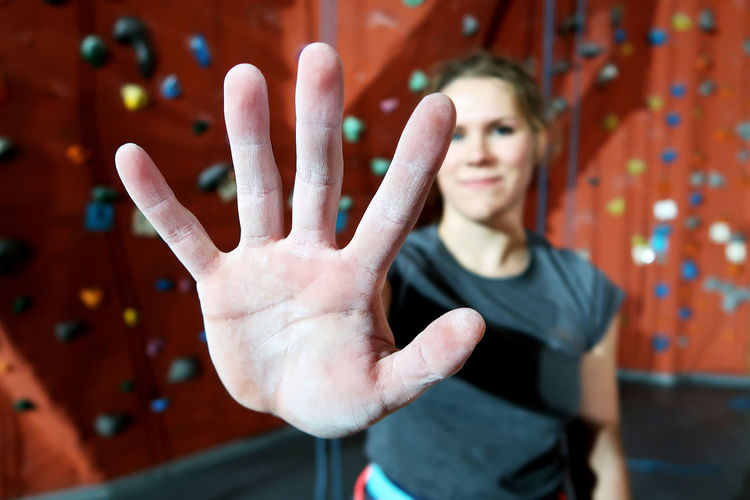 Young woman gesturing stop sign against climbing wall