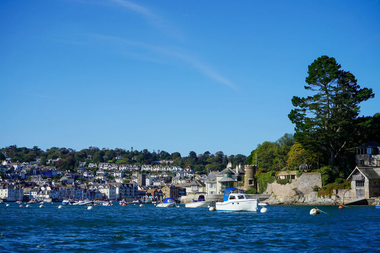 View of townscape by sea against blue sky
