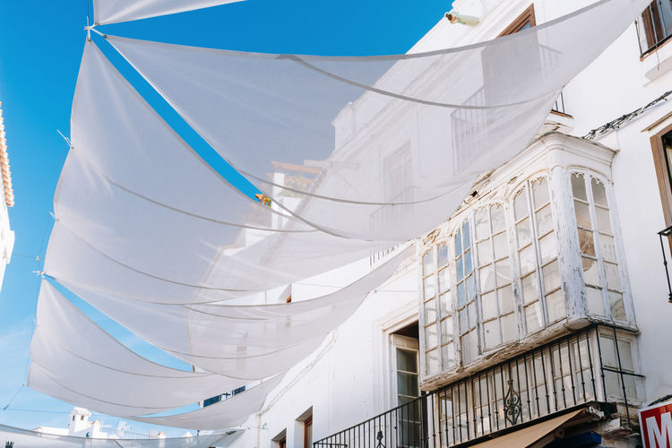 Low angle view of curtain by building against blue sky