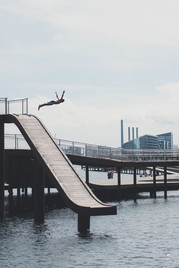 Silhouette man jumping by pier in sea