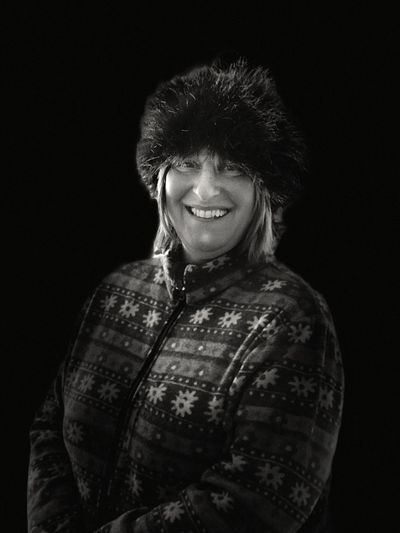 Portrait Of Mature Woman Smiling While Wearing Fur Hat Against Black Background
